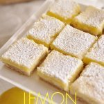 Lemon cheesecake bars on a cake stand
