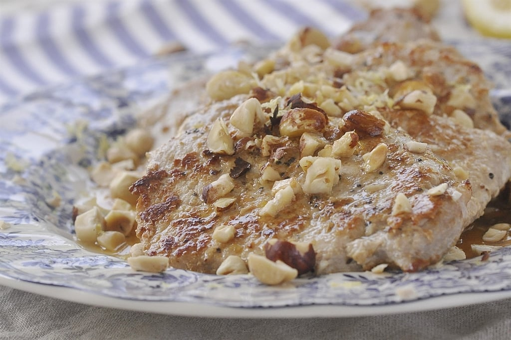 lemon pork chops topped with chopped hazelnuts