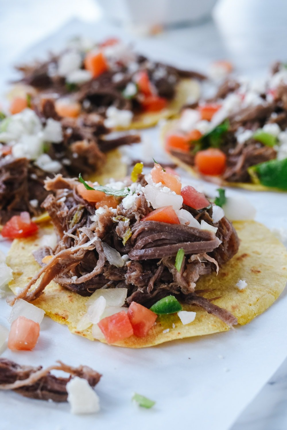 shredded beef tacos on parchment paper
