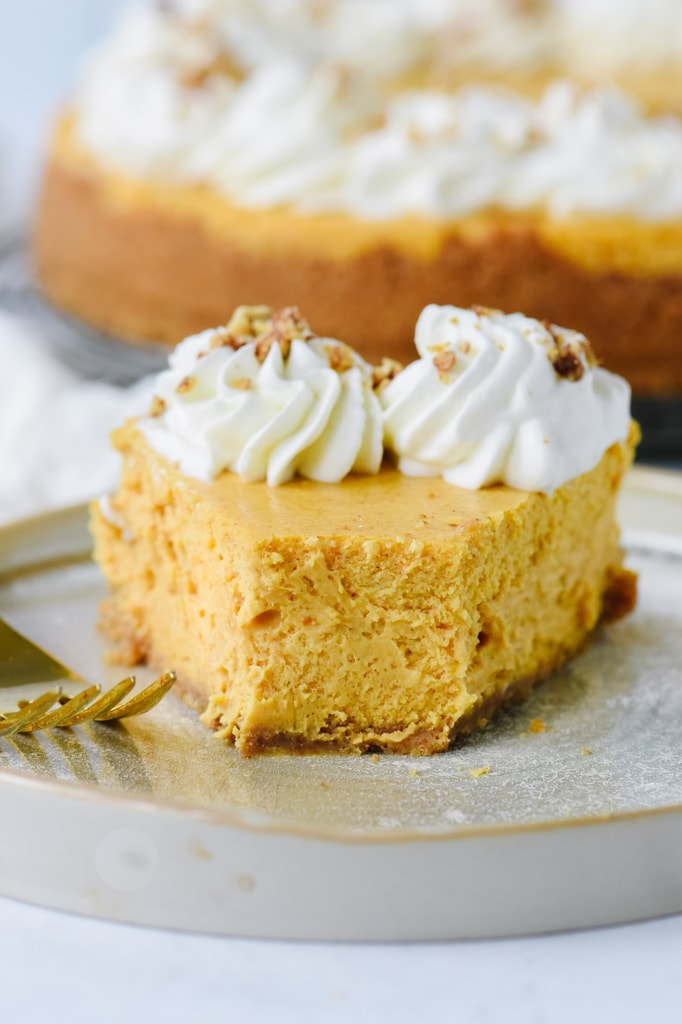 Slice of pumpkin cheesecake with a bite out of it