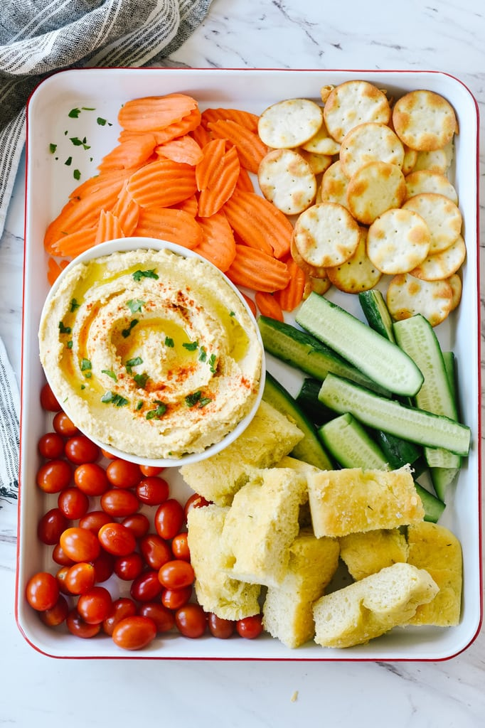 tray of hummus bread veggies and chips