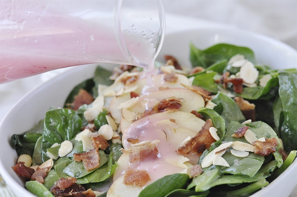 pouring dressing over spinach apple salad