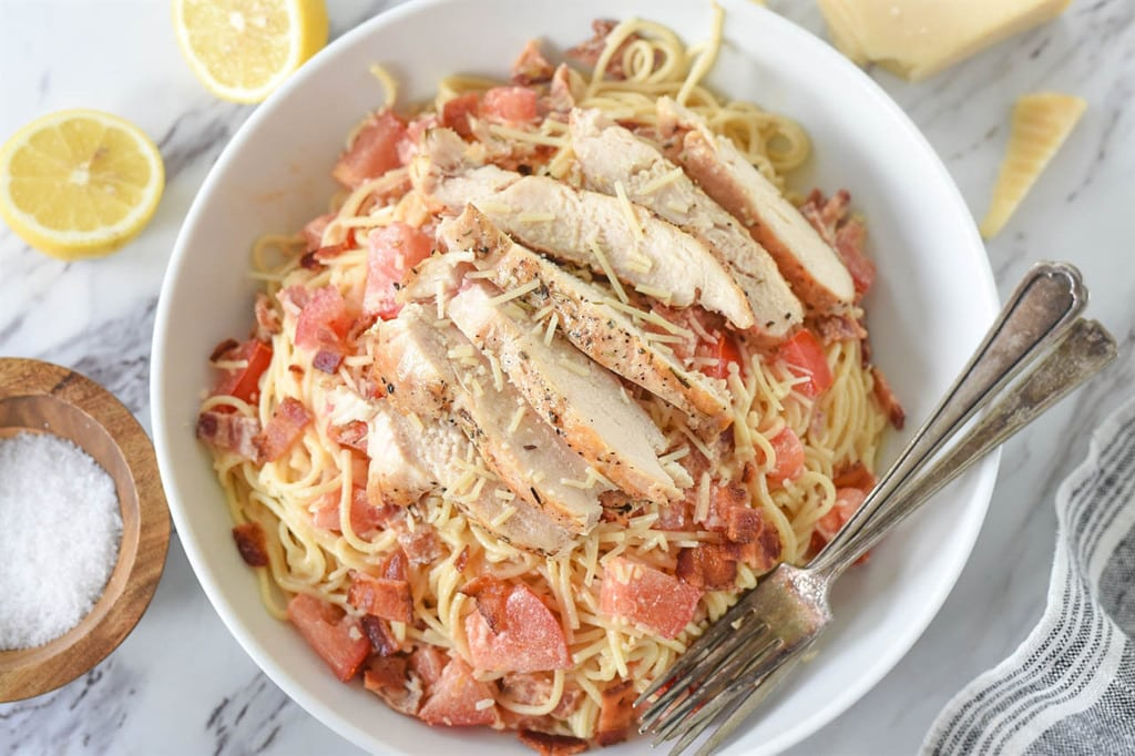 lemon pasta topped with lemon chicken in a serving dish