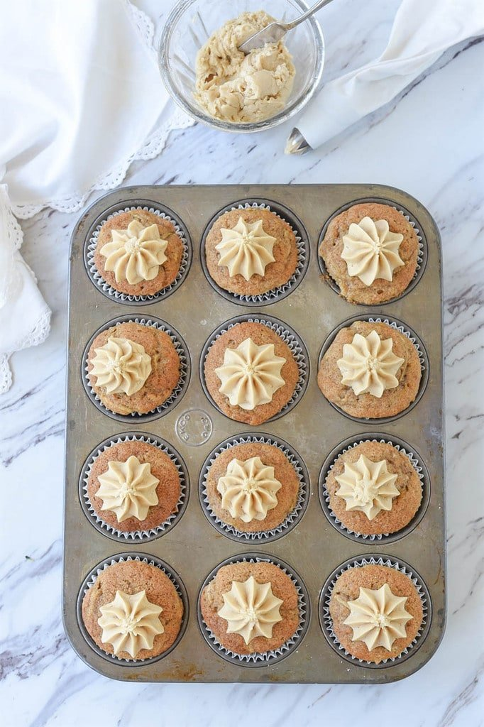 12 zucchini cupcakes with caramel frosting in a muffin tin