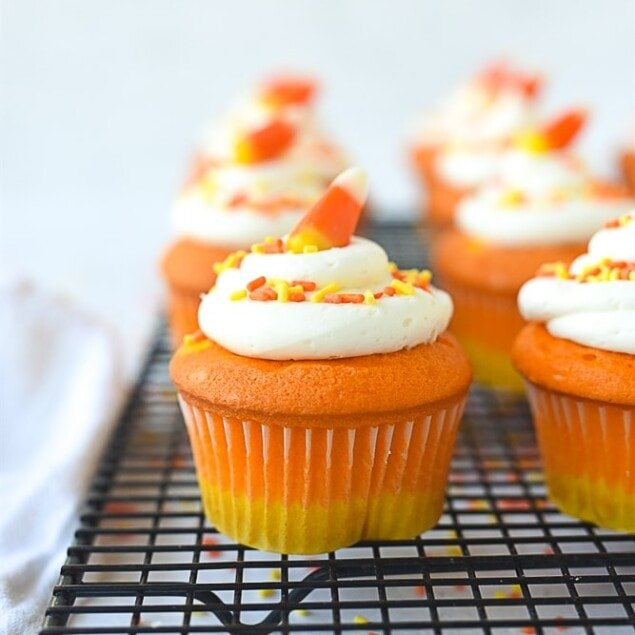 candy corn cupcake on a cooling rack