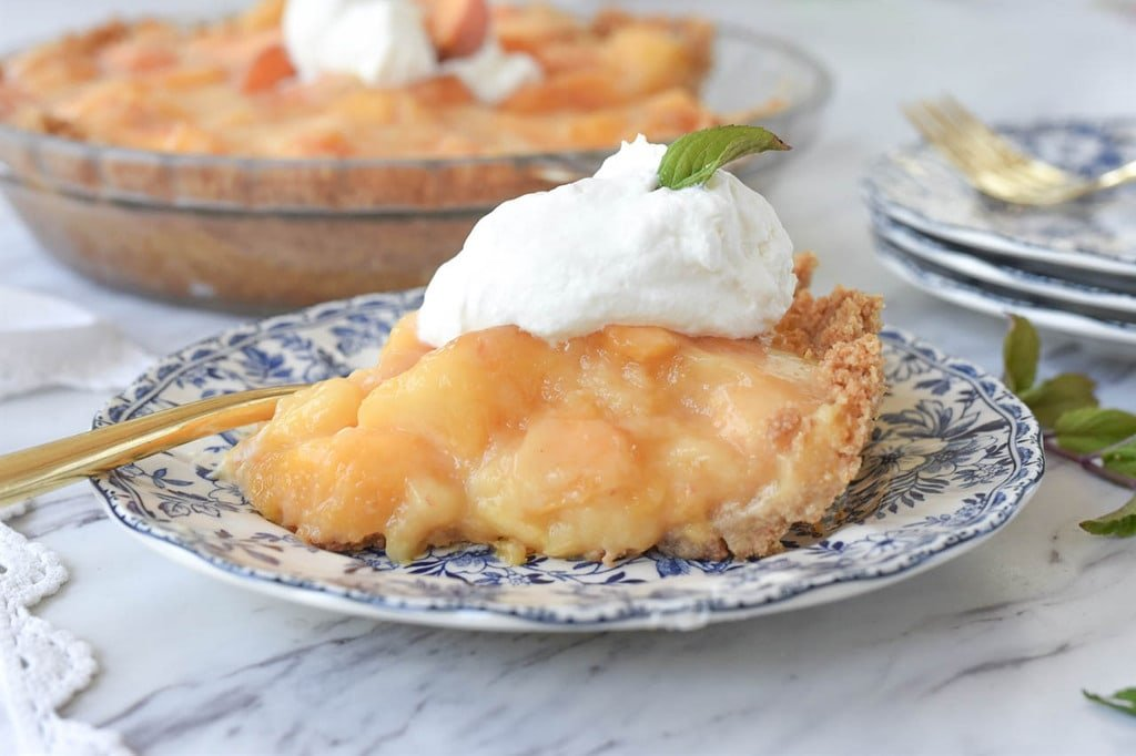 slice of fresh peach pie on a plate
