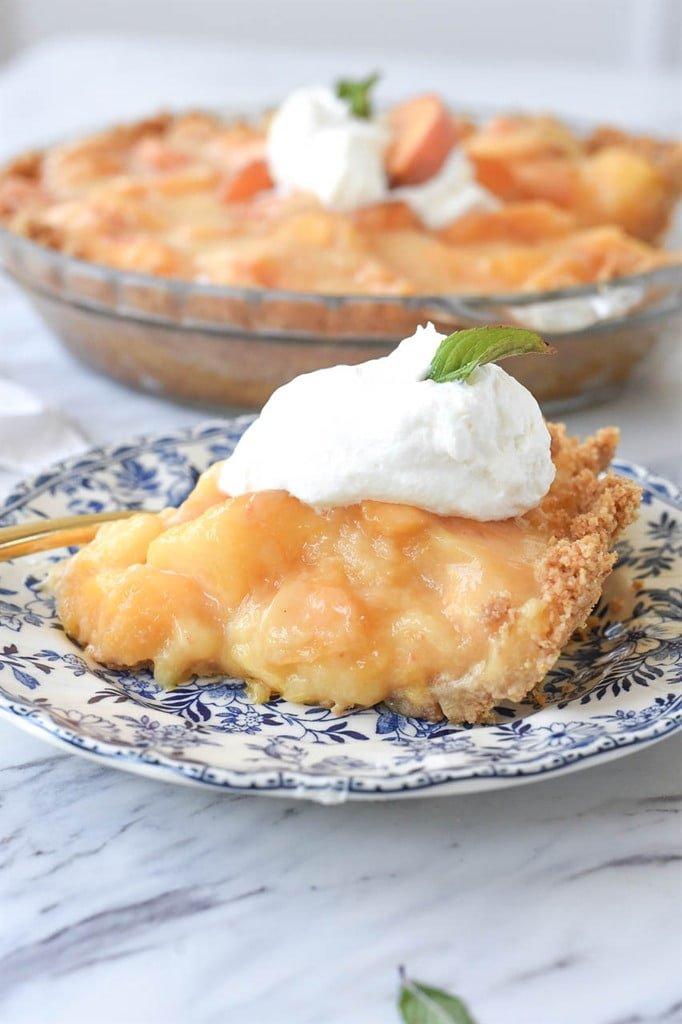 slice of fresh peach pie topped with whipped cream