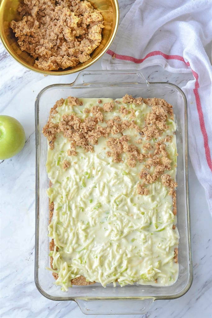 sour cream and sliced apples topped with crumble in 9 by 13 pan