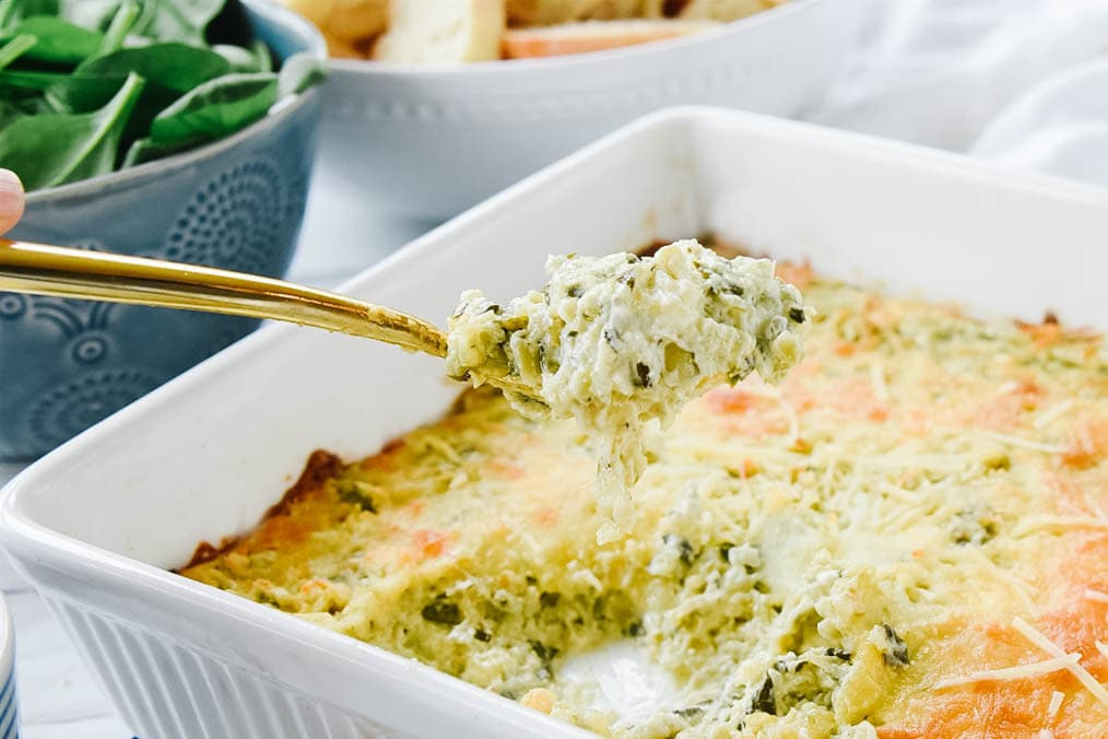 serving Spinach Artichoke Dip with a gold spoon