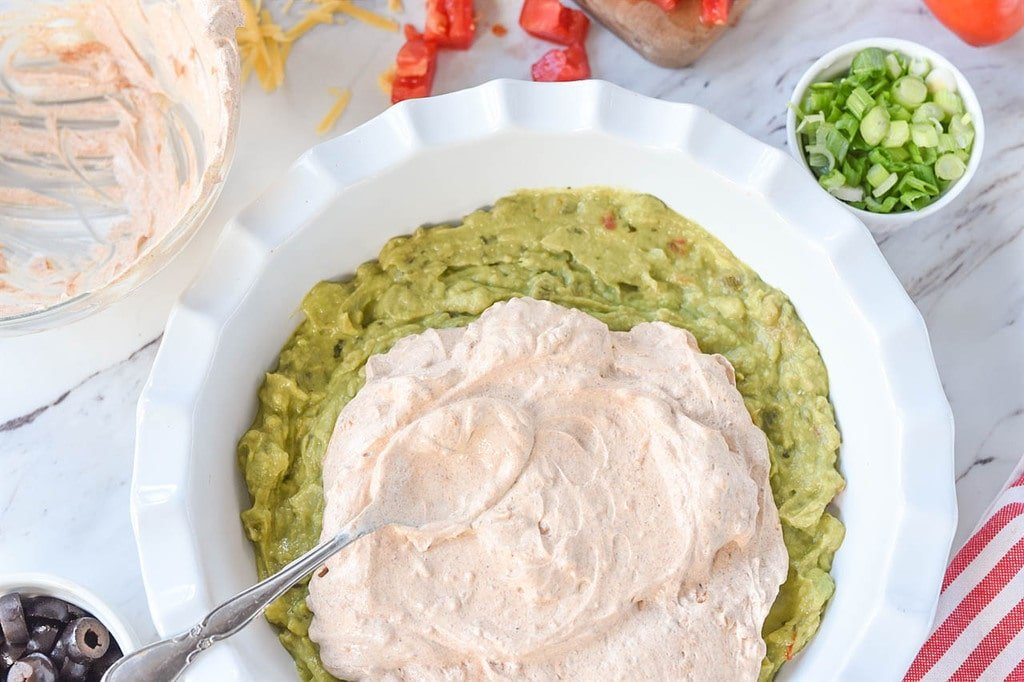 spreading sour cream over guacamole for seven layer dip