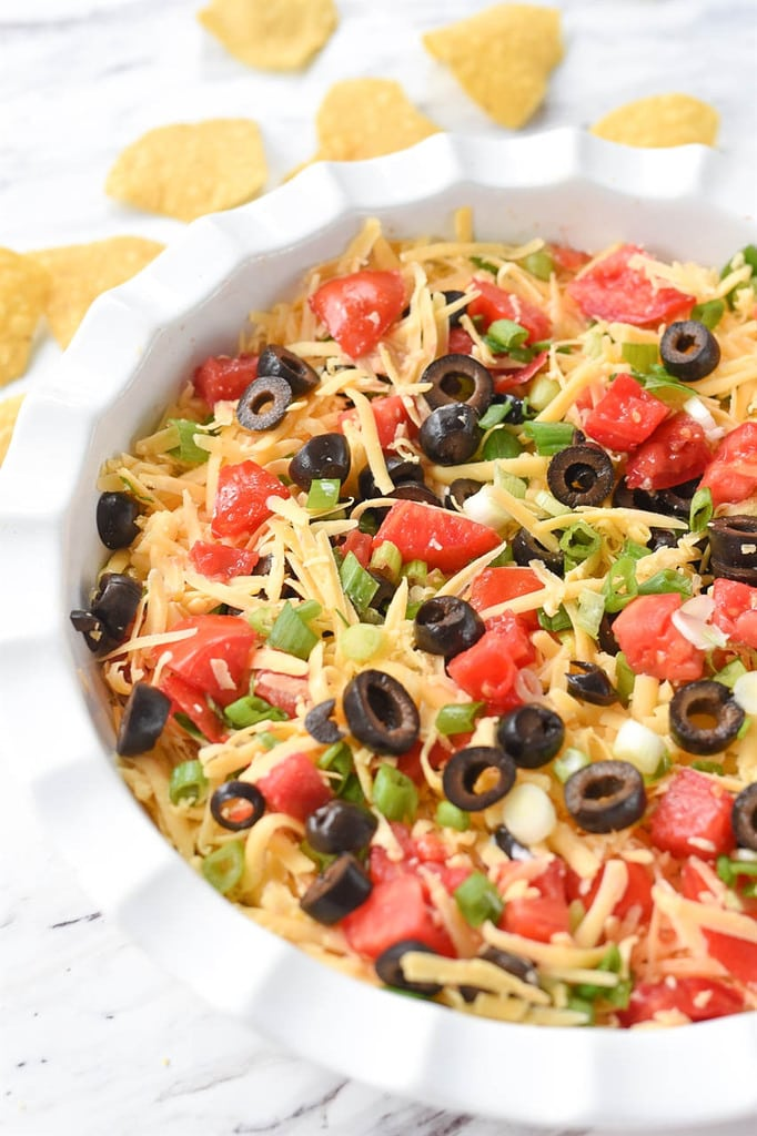 Seven Layer Dip in a white dish with tortilla chips