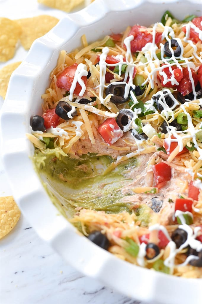 Seven Layer Dip drizzled with sour cream