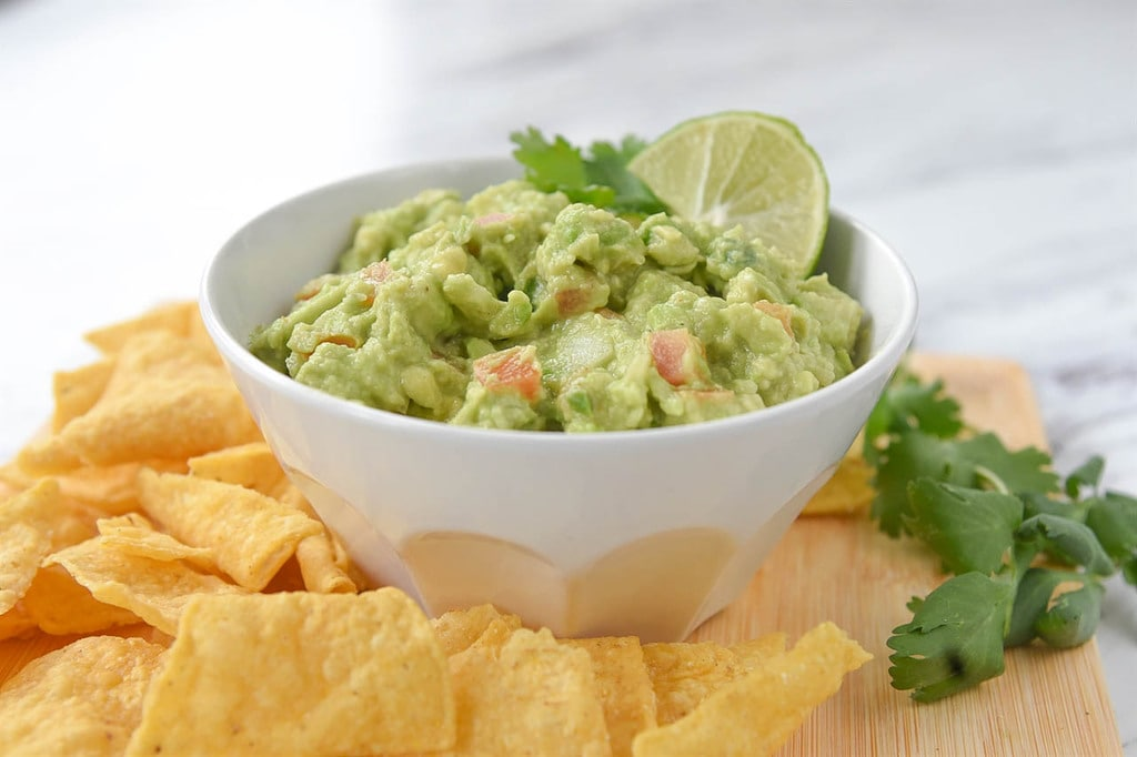 Guacamole in a bowl and chips on a board