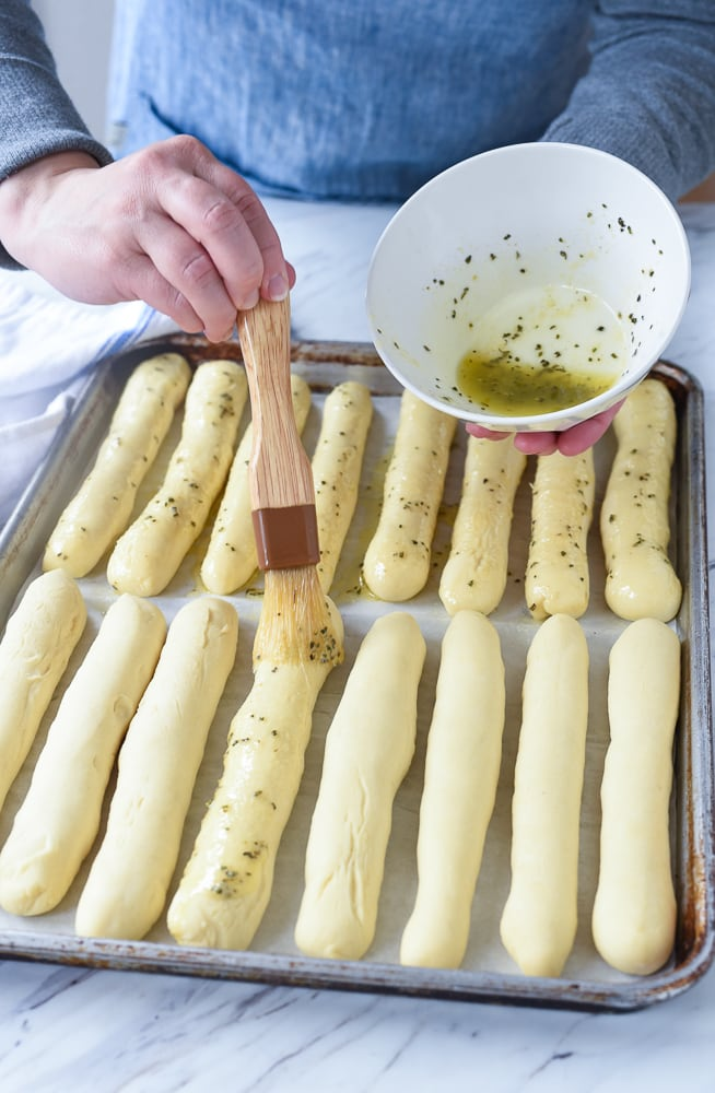 brushing butter on breadsticks
