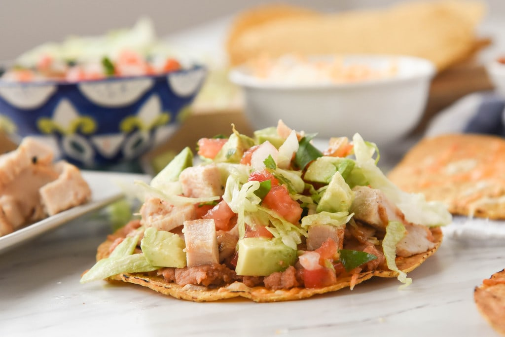 Chicken Tostada with beans lettuce tomato and avacado