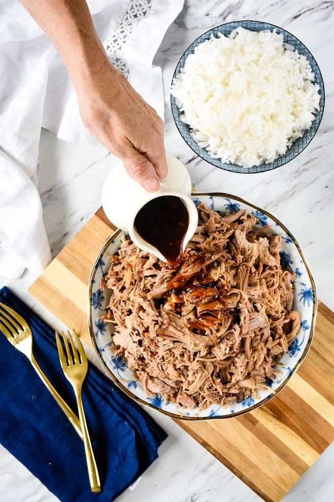 pouring BBQ sauce over Kalua Pork