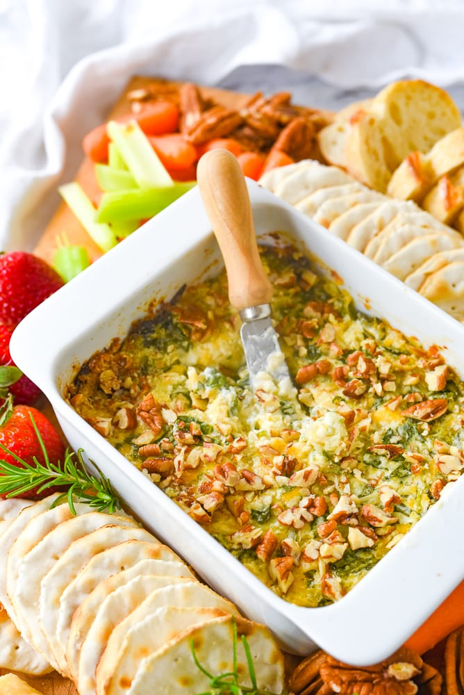 dish of artichoke dip with pecans on top