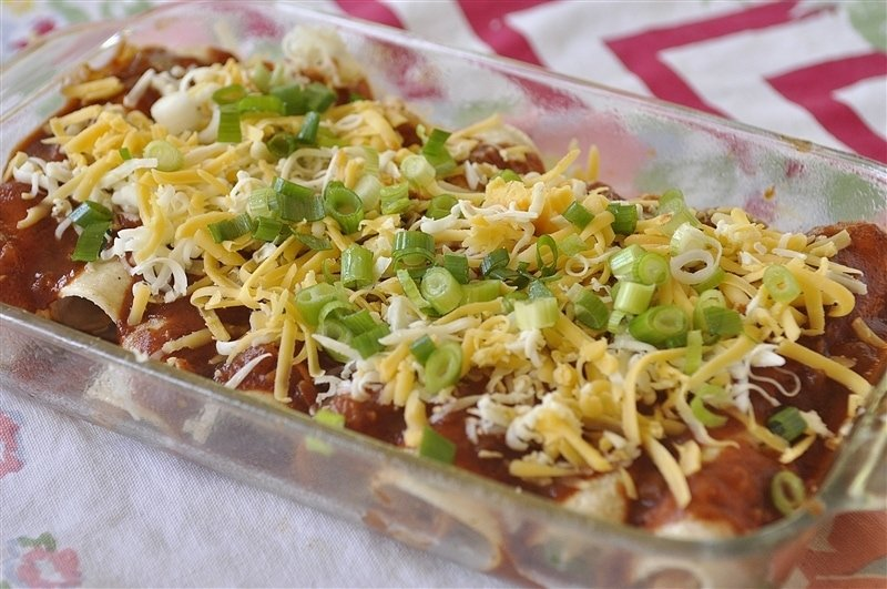 chicken enchiladas topped with homemade enchilada sauce cheese and green onions