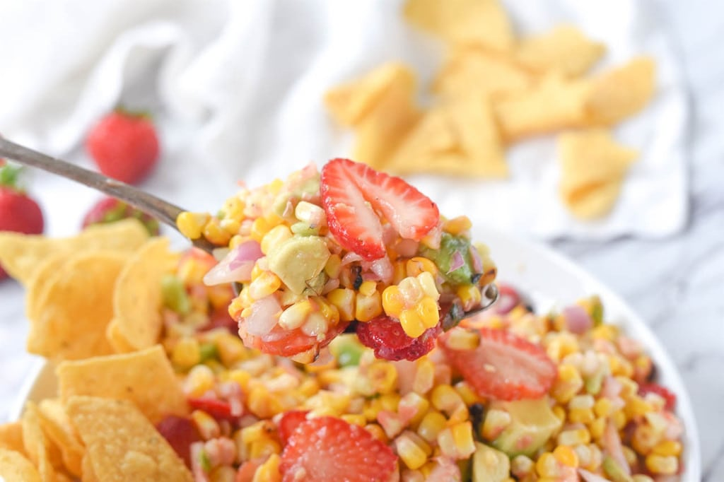 spoon full of roasted corn salsa with strawberries and avacado