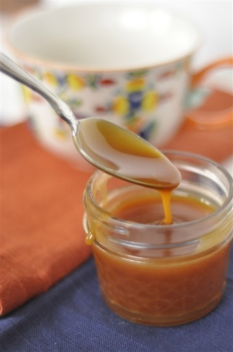 carmel sauce dripping from a spoon to the jar