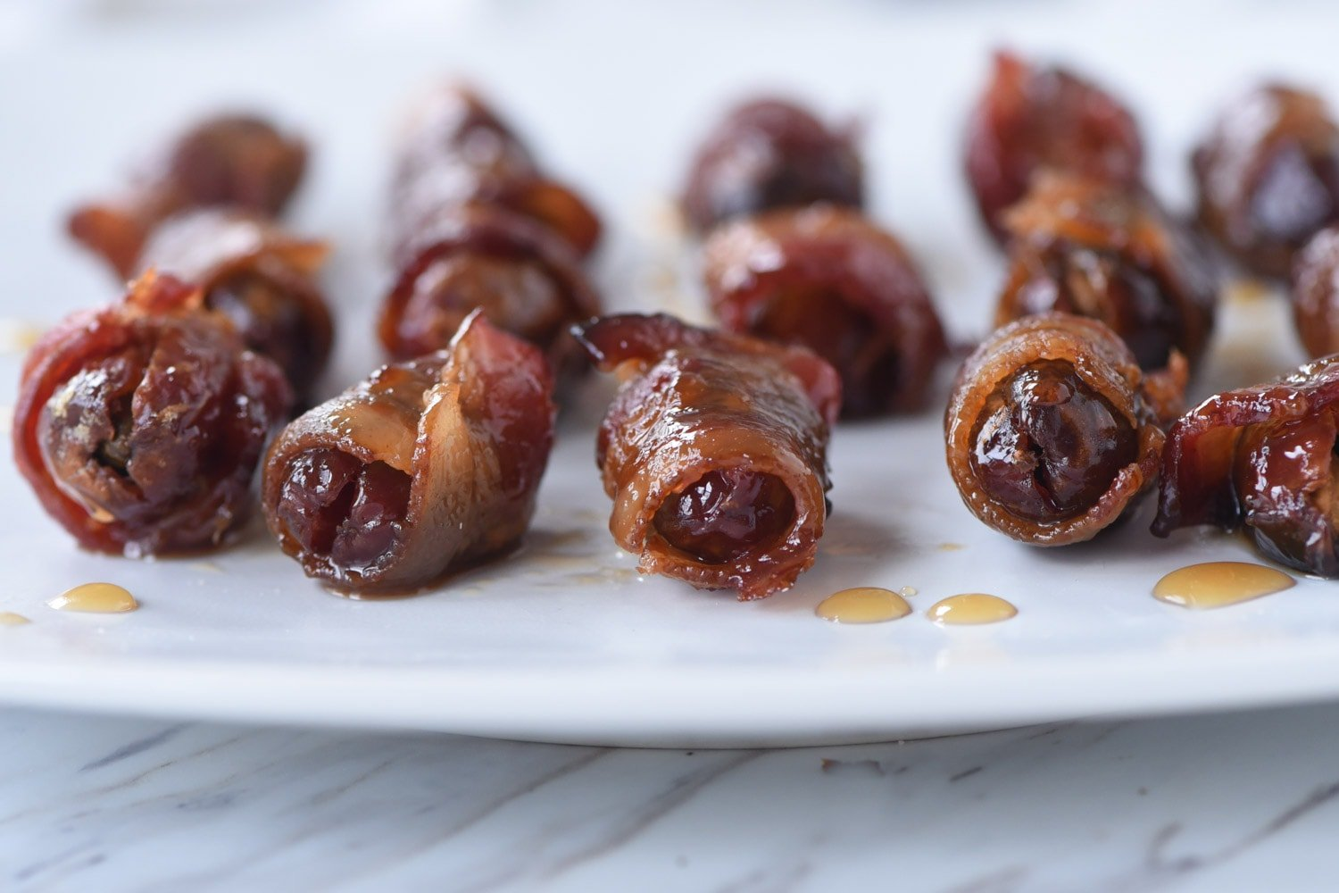 bacon wrapped dates on a white plate.