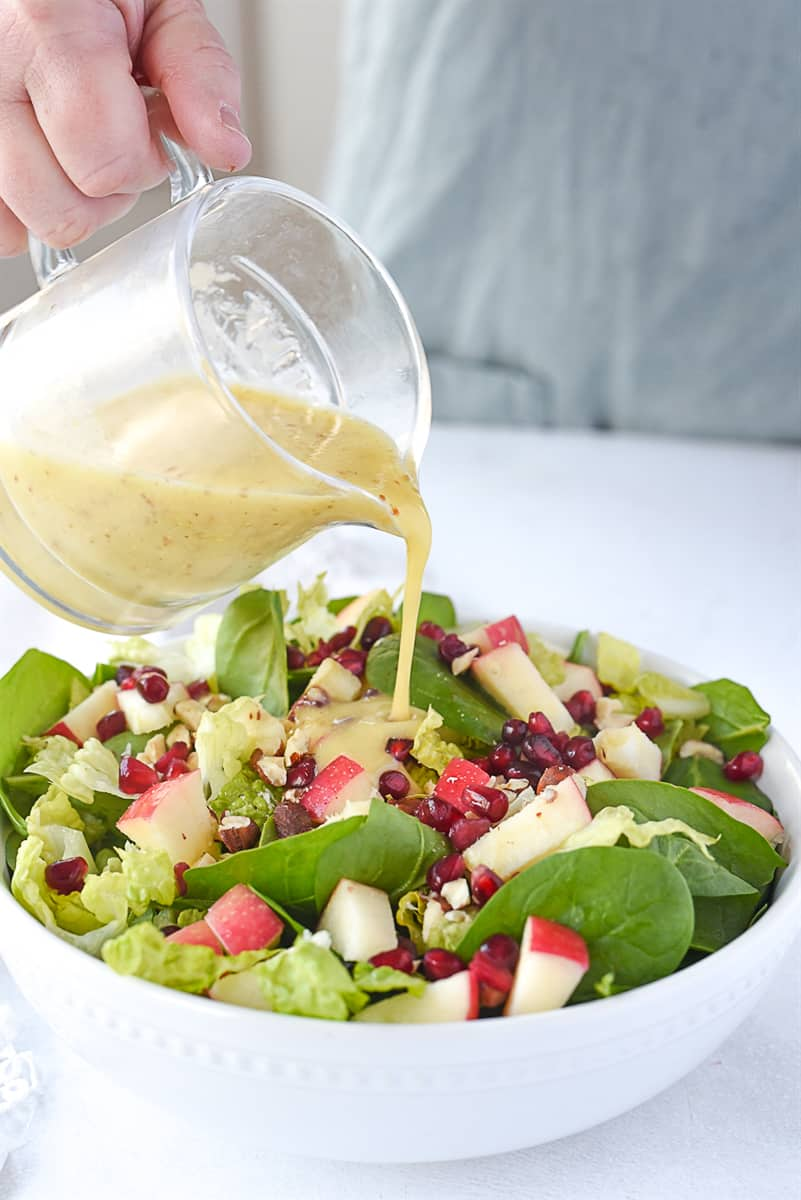 pouring salad dressing on salad