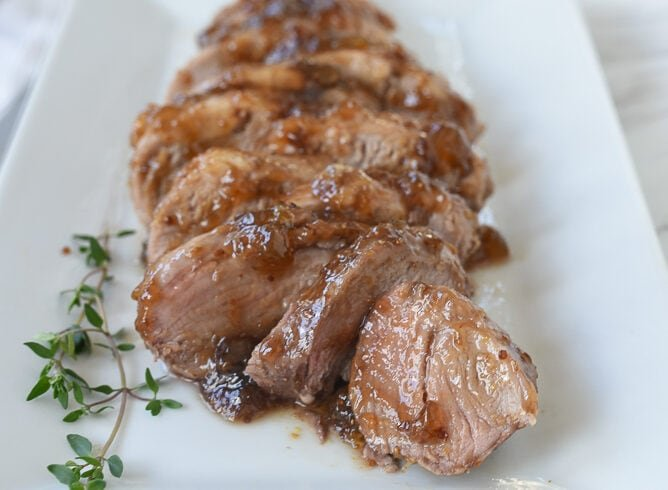sliced fig glazed pork tenderloin on a plate.