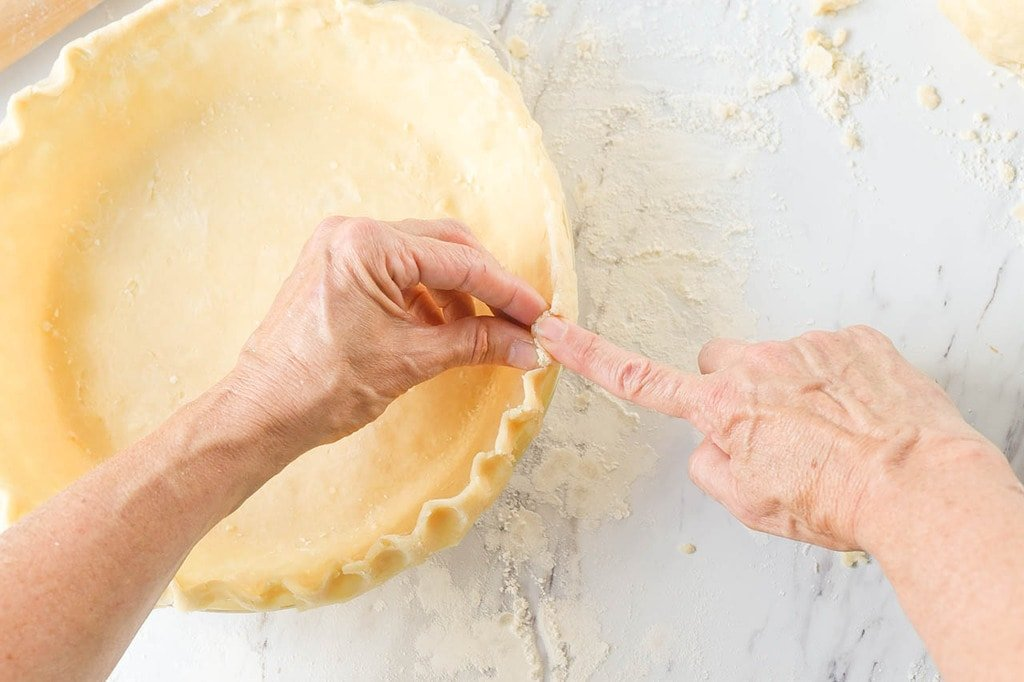 hands crimping pie crust edges