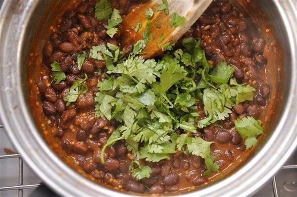 adding cilantro to pot of black beans