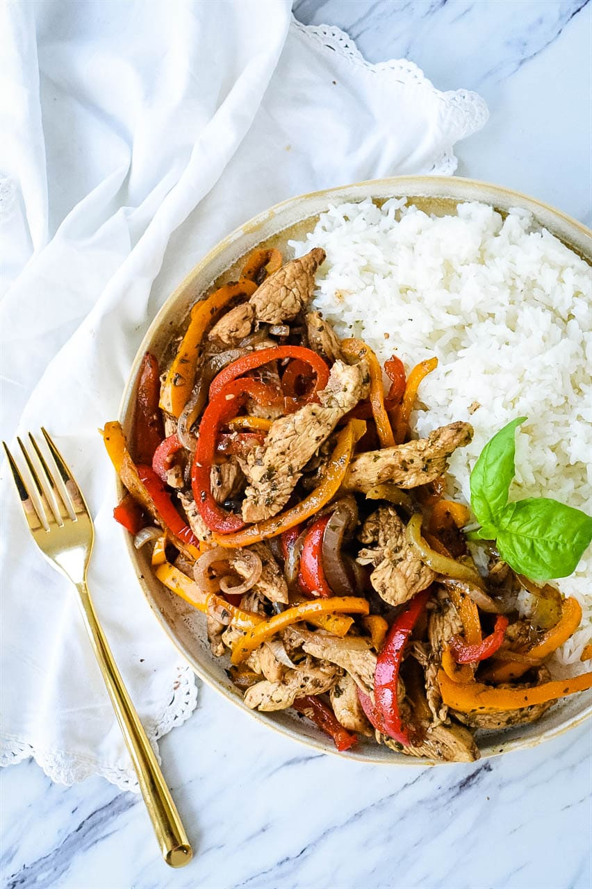 overhead shot of chicken and peppers in a bowl of rice