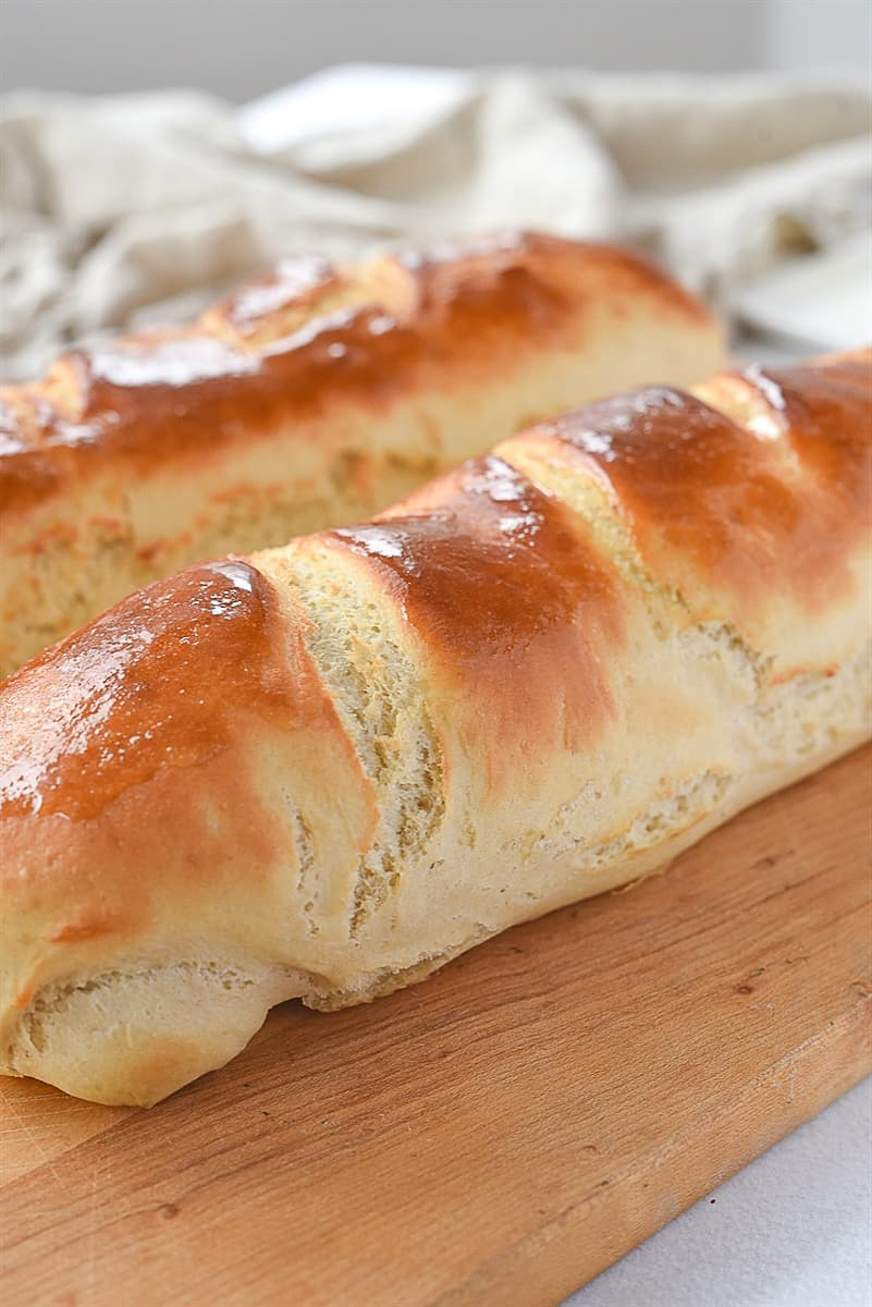 two loaves of french bread on a board