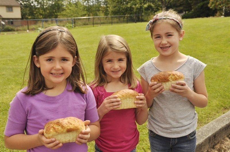 kids showing off the loaf of bread they baked