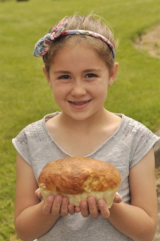 child holding a loaf of bread