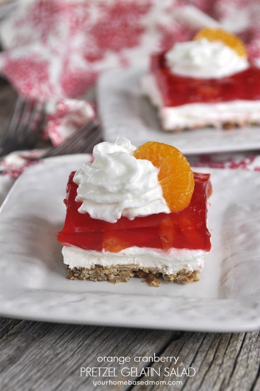 Orange Cranberry Pretzel Salad topped with whipped cream and mandarin orange
