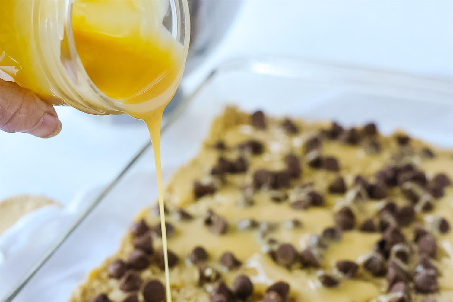pouring caramel over carmelitas