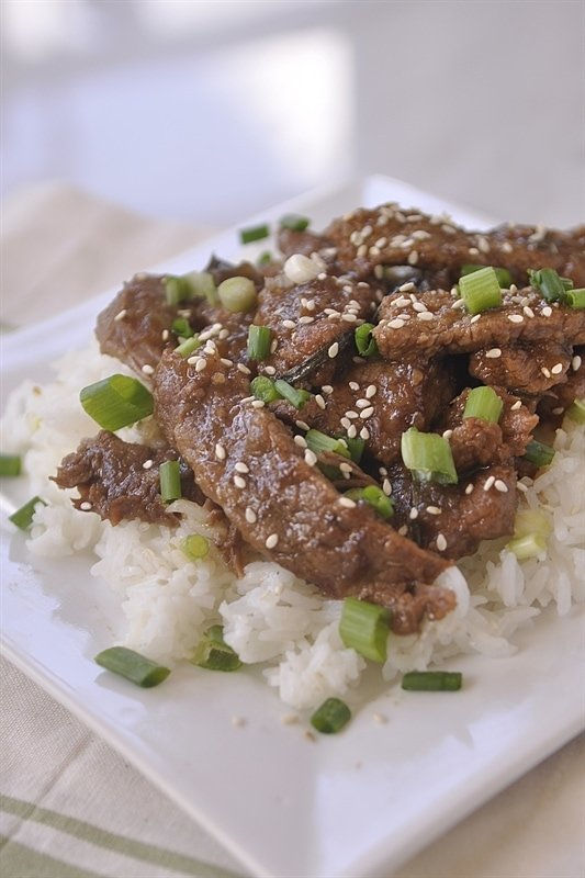 slow cooker mongolian beef topped with sesame seeds and green onions
