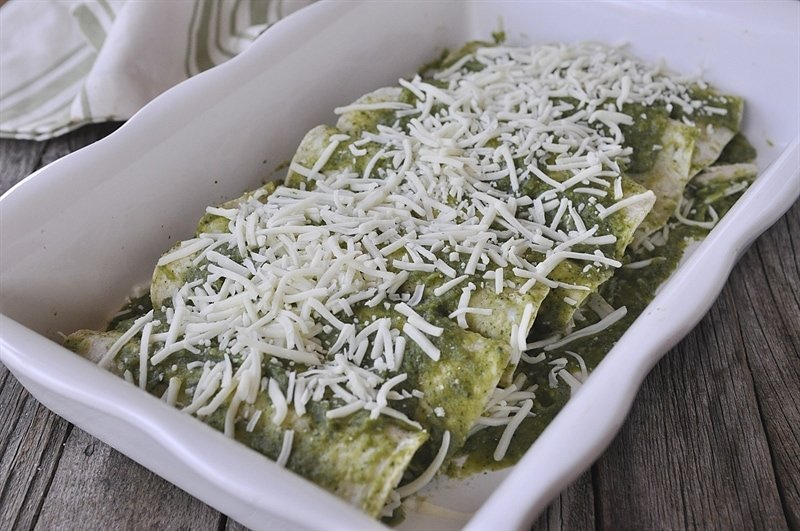 chicken chile verde enchiladas covered in shredded cheese