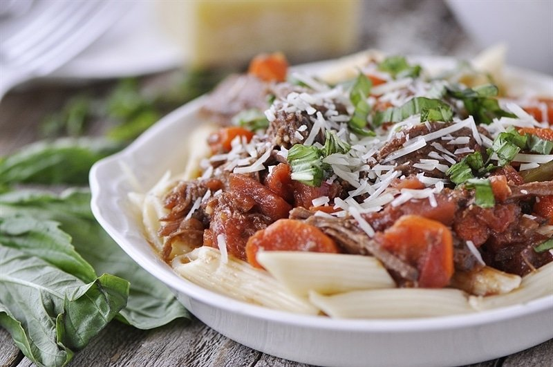 Slow Cooker Beef Ragu garnished with cheese and basil