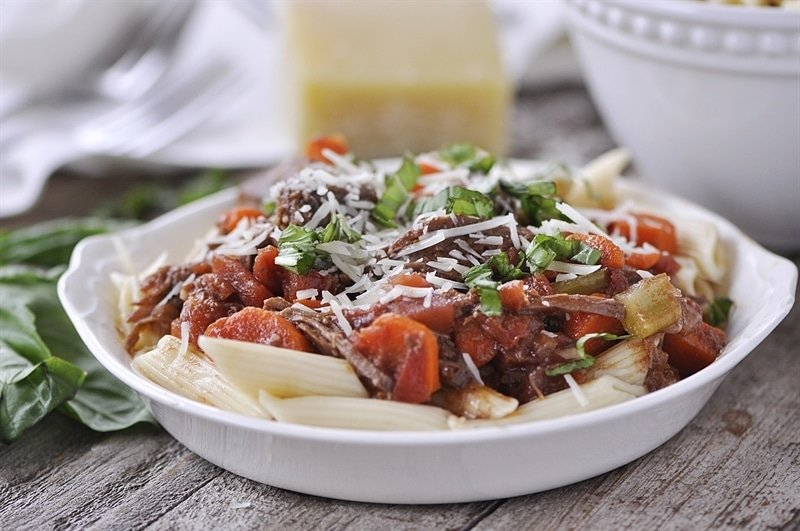 Slow Cooker Beef Ragu topped with parmesan and basil