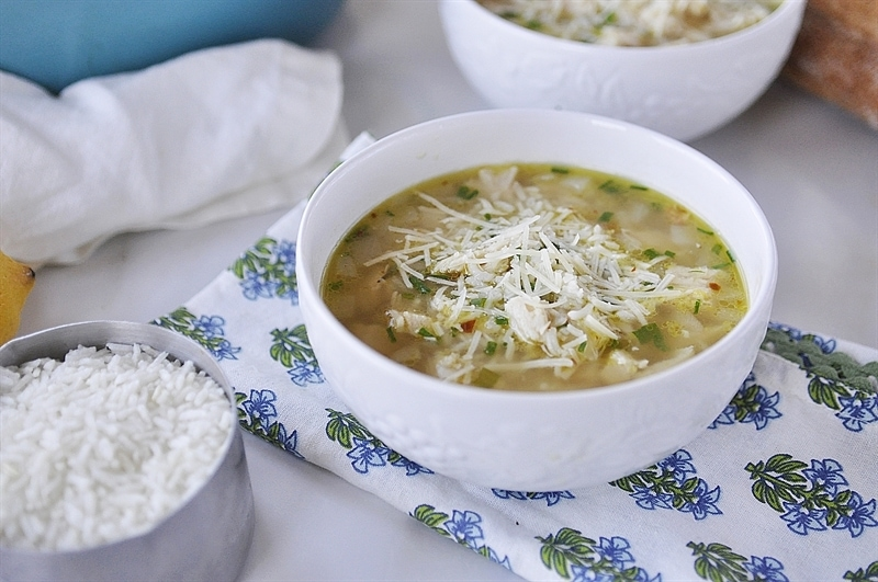 warm bowl of lemon chicken and rice soup topped with freshly grated Parmesan