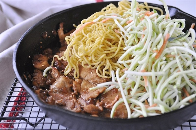 pan of stir fry chicken with yakisoba noodles and slaw