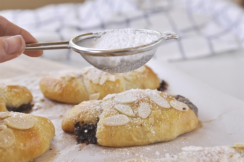 dusting Chocolate Almond Croissant with powdered sugar