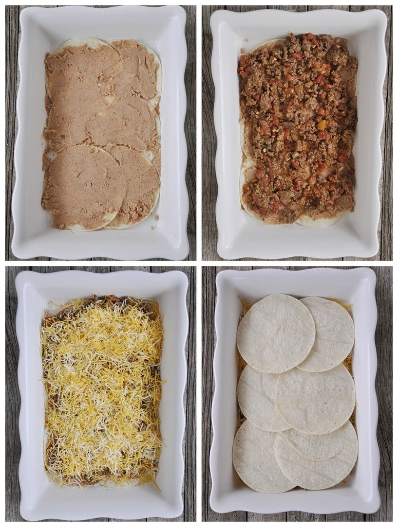 corn tortillas refried beans taco meat and cheese layered in a white casserole dish