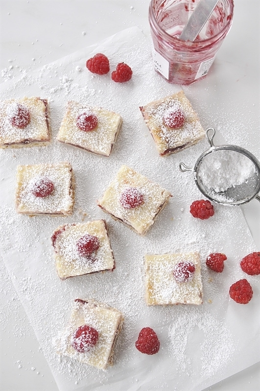 Raspberry Lemon Cheesecake Bars topped with powdered sugar and a raspberry.