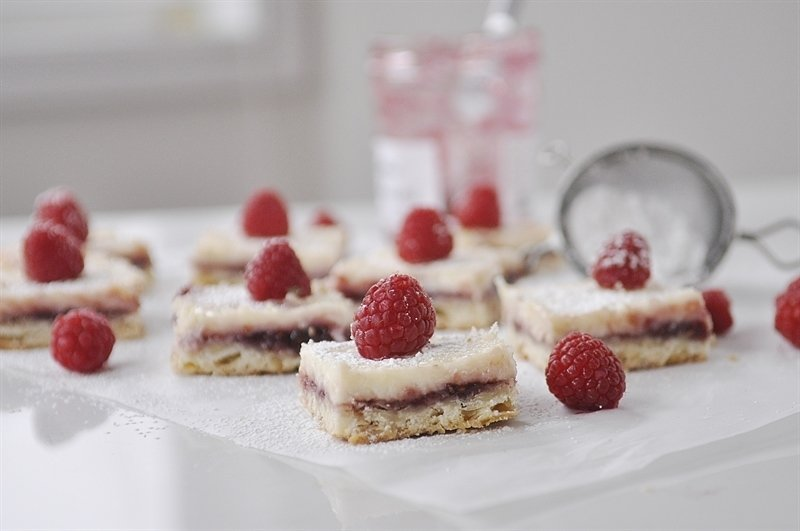Raspberry Lemon Cheesecake Bars dusted with powdered sugar
