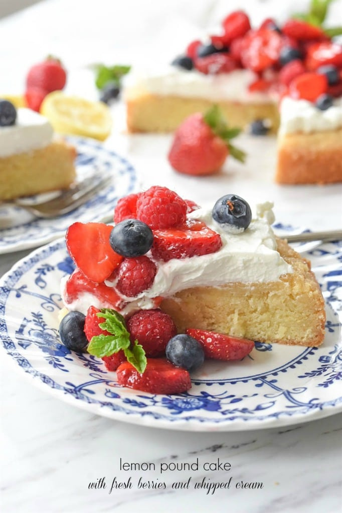 A slice of Lemon poundcake topped with fresh berries and whipped cream