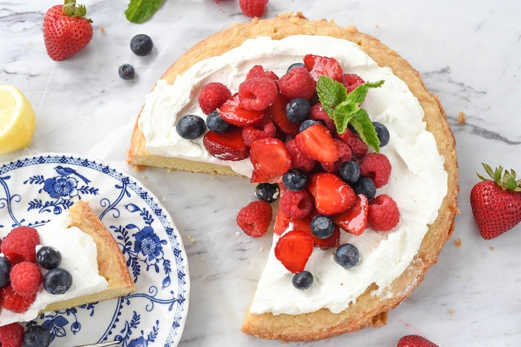 a slice of lemon pound cake served with whipped cream and fresh berries
