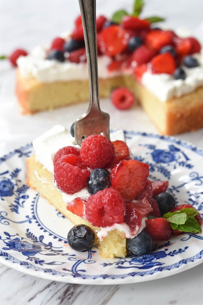 a fork stuck in a slice of lemon pound cake topped with berries