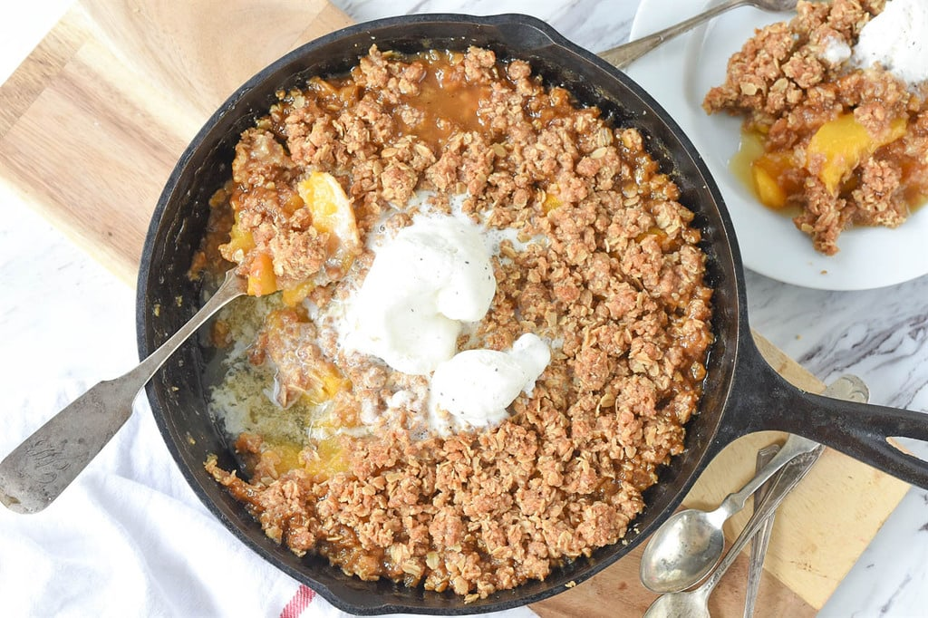eating Peach Crisp with ice cream out of a cast iron skillet