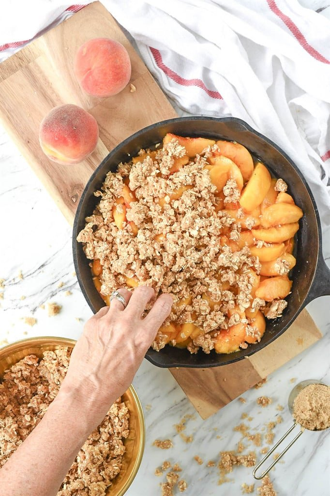 adding crumble to cast iron peach crips